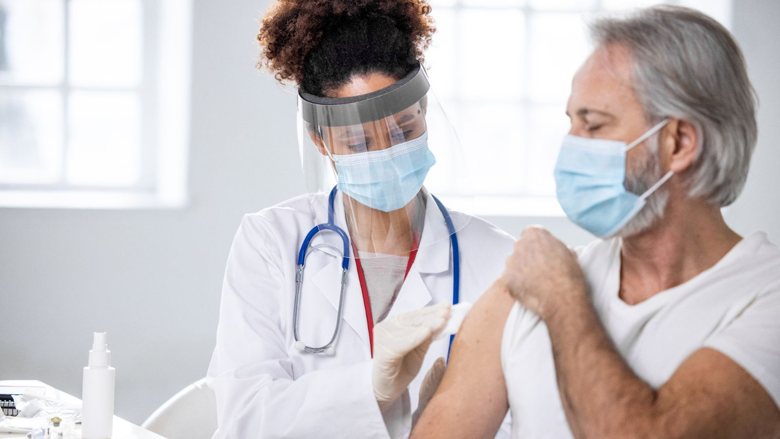 Partial front view of mature Caucasian male patient watching as healthcare worker in lab coat, surgical mask, and face shield swabs injection site.