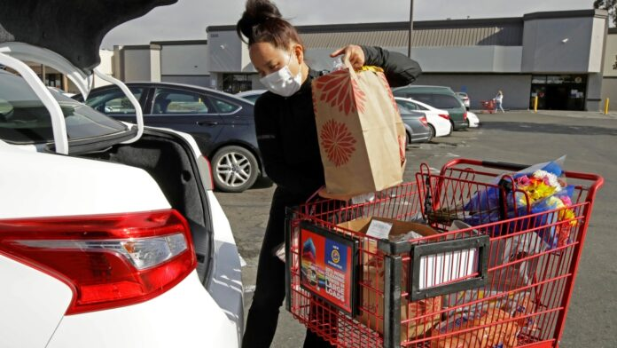In this July 1, 2020 file photo, Instacart worker Saori Okawa loads groceries into her car for home delivery in San Leandro, Calif.